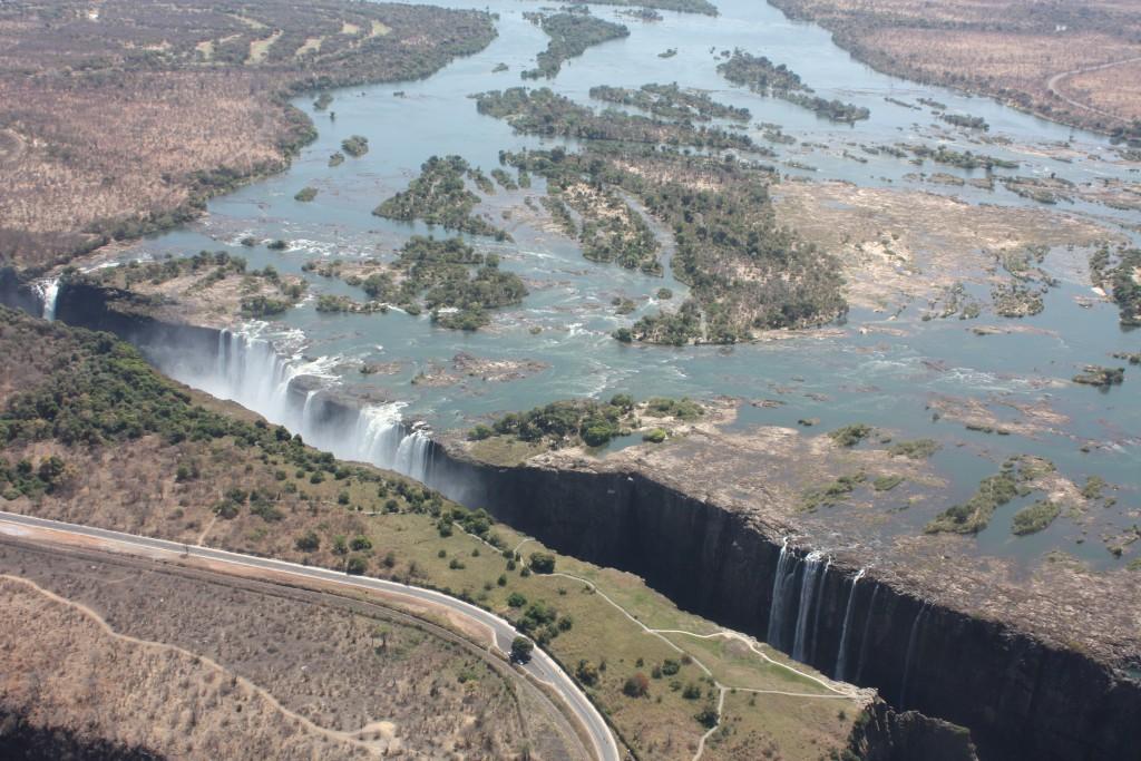 Victoriafallene sett fra helikopter. Zimbabwe i forgrunnen, Zambia på andre siden av kløften.